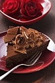 Piece of chocolate cake with chocolate curls, red roses