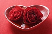 Red roses in heart-shaped bowl