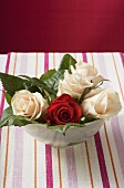 Roses in bowl on striped tablecloth