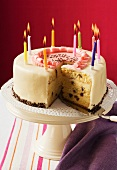 Birthday cake with burning candles, a piece cut