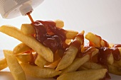 Squirting ketchup from a bottle onto chips