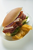 Salami, ham, cheese and salad sandwich with crisps