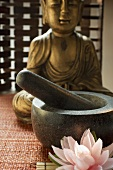 Mortar with pestle in front of Buddha (Asia)