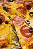 Pizza with salami, cheese and olives, a piece cut (detail)