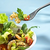 Salad leaves with shrimps on fork and in dish