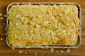 Bee sting cake with flaked almonds in aluminium baking tin