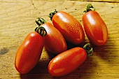 Five grape tomatoes on wooden background