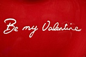 The words Be my Valentine on red plate (close-up)