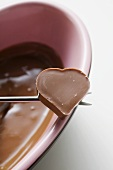 Schokoladenfondue mit Herzpraline auf Fonduegabel