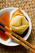 A deep-fried wonton with two sauces (close-up)
