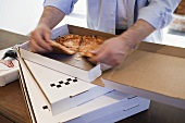 Man dividing up Pizza Margherita in pizza box