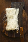 Thin rice noodles on wooden plate with Asian cleaver