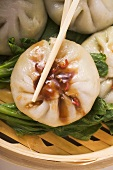 Filled yeast dumplings with hoisin sauce on pak choi (Thailand)