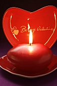 Red candle and heart-shaped plate for Valentine's Day