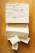 Tofublock, Tofuscheibe und Tofuwürfel auf Holzuntergrund