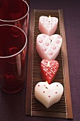 Heart-shaped candles and red glasses for Valentine's Day