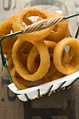 Deep-fried onion rings in a wire basket