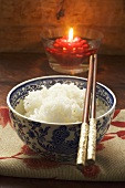 Bowl of rice in front of floating candle (Asia)
