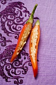 Red chili pepper, halved, on purple fabric