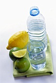 Still water in bottle and glass beside lemon and limes