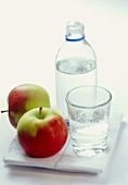 A bottle and a glass of mineral water, apples beside them