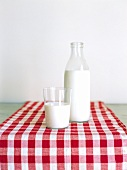 Glass and bottle of milk on red and white checked fabric