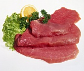 Three raw veal escalopes, lettuce, parsley, half a lemon