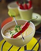 Chili pepper on fondue stick above cheese and chili sauce