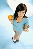 Young woman standing on scales with chocolate bar & orange