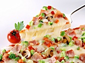 Piece of pizza with vegetables, mushrooms, ham,cheese on server