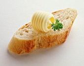 A slice of baguette with butter curl and parsley