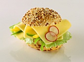 Roll with cheese, peppers, radishes and lettuce leaf