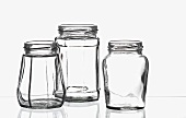 Three empty preserving jars on a sheet of glass