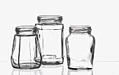 Drei leere Einweckgläser auf einer Glasplatte