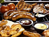 Tableau of barbecue food, sauces and rolls