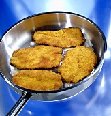 Four breaded pork escalopes being fried in a frying pan