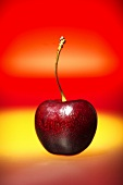 A sweet cherry against a red and yellow background