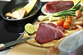 Tuna steak with vegetables and lime on wooden board