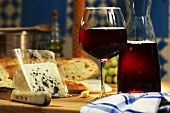 Red wine in glass and carafe and a piece of gorgonzola