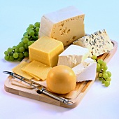 Several types of cheese on a wooden board