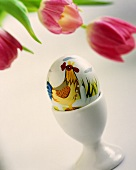 A painted Easter egg with tulips in the background