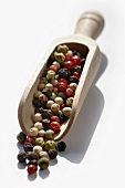 Coloured peppercorns in a wooden scoop