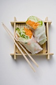 Two Vietnamese rice paper rolls with chopsticks