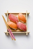 Nigiri sushi with chopsticks on bamboo mat