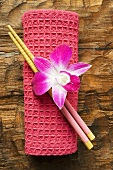 Asian table accessories: hand towel, chopsticks and orchid