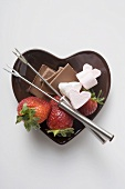 Heart-shaped bowl with ingredients for chocolate fondue