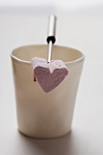 A heart-shaped marshmallow on a fondue fork resting on a mug
