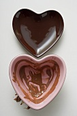 Two heart-shaped bowls, one with remains of chocolate sauce