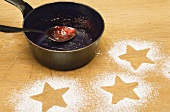 Star shapes outlined in icing sugar and saucepan with jam