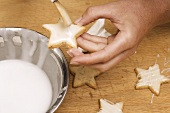 Brushing star-shaped biscuits with glacé icing